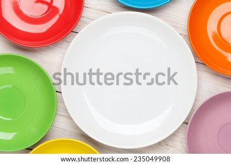 Colorful plates over wooden table background - stock photo