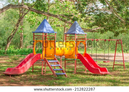 Colorful playground under big green tree