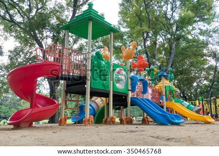 Colorful playground with children and parents in park
