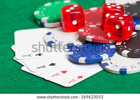 colorful playing poker chips, dice and cards on the green table