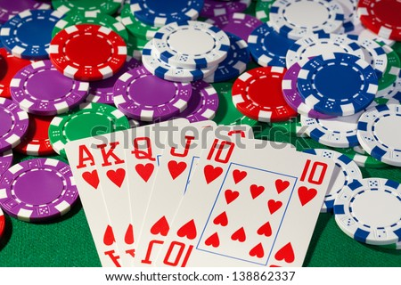 Colorful poker chips and royal flush closeup on green cloth