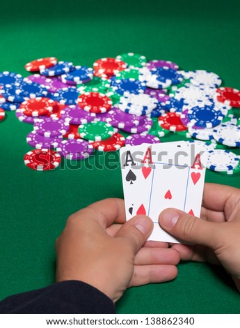 Colorful poker chips and two Ace closeup on green cloth