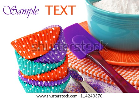 Colorful polka dot cupcake wrappers with color coordinated baking supplies on white background with copy space.  Closeup with shallow dof. - stock photo