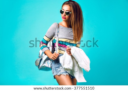 Colorful portrait of gorgeous stylish blonde woman, fluffy hairs bright make up, casual outfit, backpack sunglasses, pastel spring colors. Glamour fashion studio. - stock photo