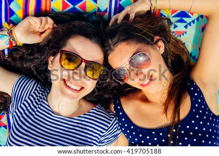 Colorful portrait of young happy girl friends with sun glasses lying on the beach - stock photo