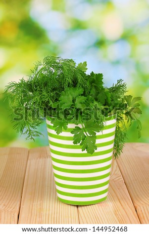 Colorful pot with parsley and dill on wooden table on natural background - stock photo
