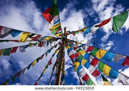 colorful prayer flag in tibet under blue sky and white cloud