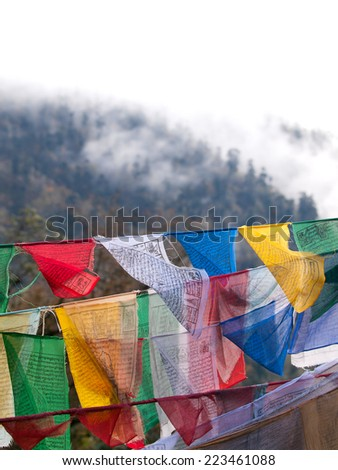 Colorful prayer flags over the misty himalayas at the Dochula Pass between Punakha and Thimpu in Bhutan - stock photo