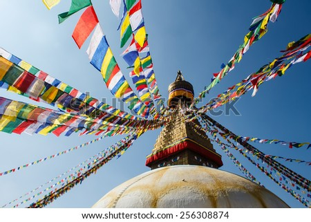 colorful praying flags and buddhist stupa in sunlight in nepal