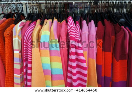Colorful pullovers on hangers. - stock photo