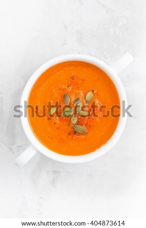 colorful pumpkin cream soup on a white background, top view, vertical - stock photo