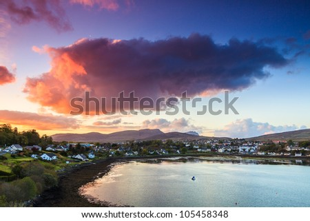 Colorful purple cloudscape at sunset  over a village - stock photo