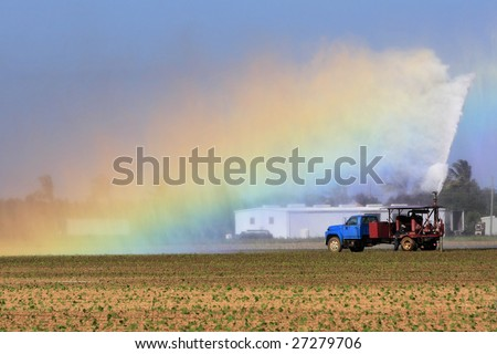 Colorful rainbow caused by the water spray during the irrigation of farmland - stock photo