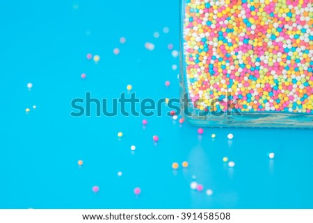 colorful rainbow sweet candies spreading pastry decoration in bottle - stock photo