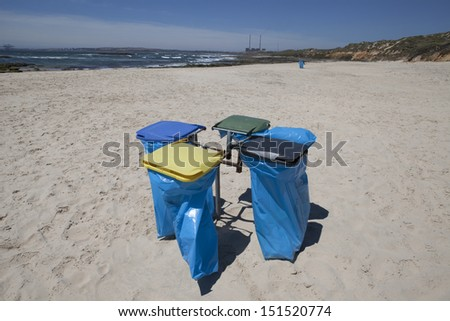 Colorful Recycle Bins on the beach. - stock photo