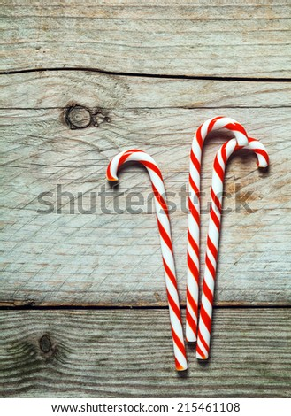 Colorful red and white striped Xmas candy canes on a rustic wooden background with copyspace for your seasonal Christmas greeting or invitation - stock photo
