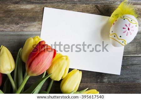 Colorful red and yellow tulips and Easter egg, with a blank card on rustic wooden table.
