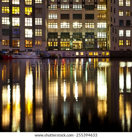 Colorful reflection of alight windows in the calm river
