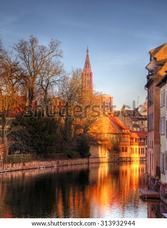 Colorful reflections of traditional houses in a small canal in Strasbourg. In the distance can be seen The Strasbourg Cathedral of Our Ladies. - stock photo