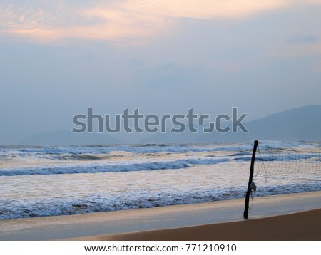 colorful relax lonesome clean tropical white sand beach sea scene with foggy blue sky and dark silhouettes of beach volleyball net for backdrop or background
