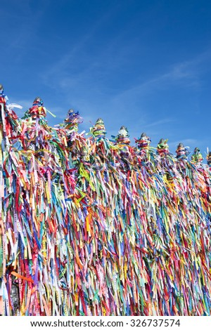 Colorful religious Brazilian wish ribbons tied on gate at the Church of Nosso Senhor do Bonfim in Salvador Brazil under bright blue sky