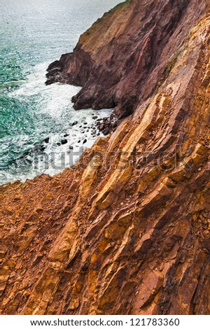 Colorful rocky steep cliffs drop off into the sea.  View is looking over the edge. - stock photo