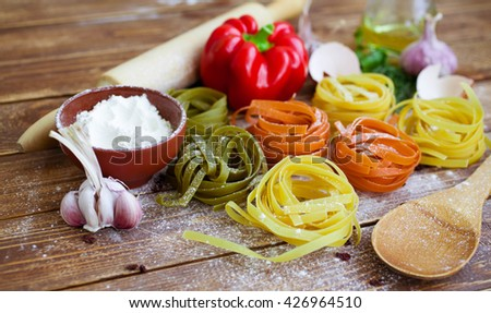 Colorful rolled pasta on the wooden background. Green, red and yellow fettuccine. Food composition on a wooden table. Italian spaghetti - stock photo