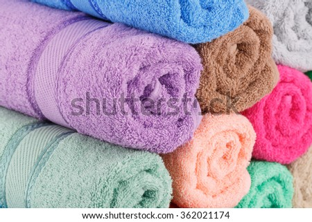 Colorful rolled towels stack closeup picture. - stock photo