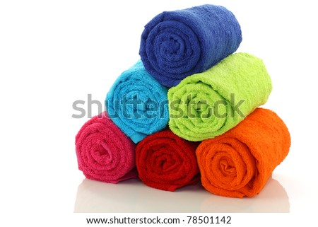 colorful rolled up and stacked bathroom towels on a white background