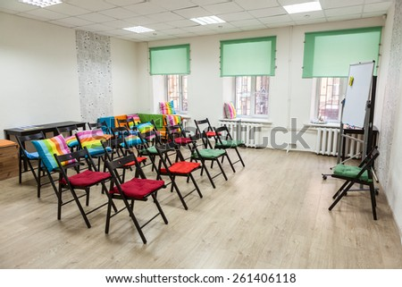 Colorful room for meeting with arranged chairs and flipchart on the floor, office space - stock photo