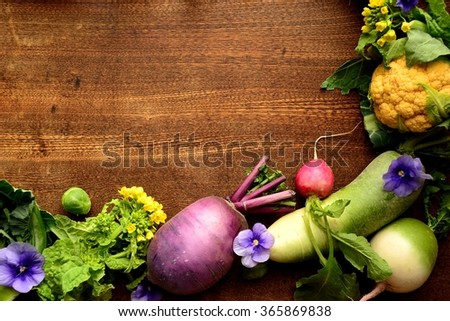 Colorful root vegetables with edible flowers on the wooden background.frame - stock photo