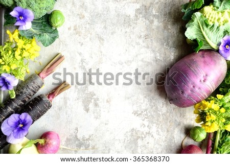Colorful root vegetables with spring edible flowers. - stock photo
