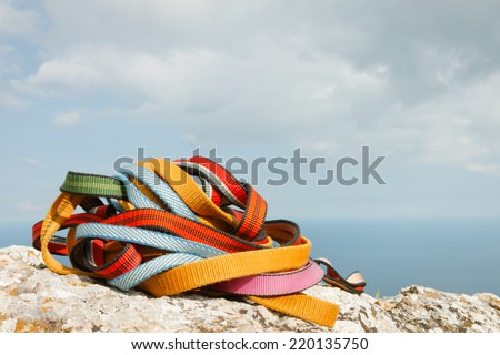 Colorful ropes on the rock. Climbing equipment - stock photo