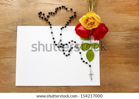 Colorful roses and black rosary on wooden background. Blank sheet of paper, copy space. - stock photo
