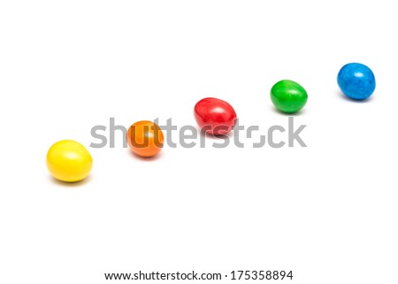Colorful Row Of Coated Chocolate Candy Close Up Isolated On White - stock photo