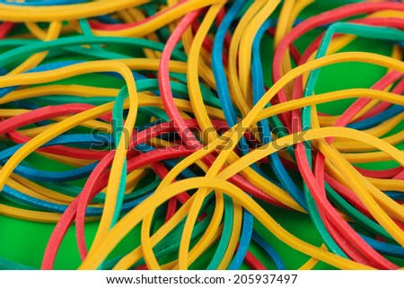 Colorful rubber bands on green background close-up