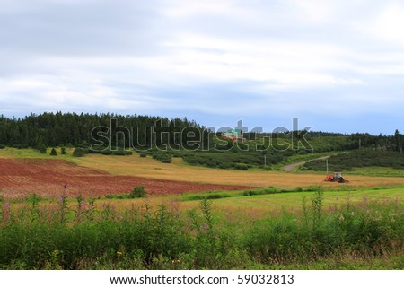 Colorful rural farmland scene with red tractor and beautiful modern house on a hill in New Brunswick, Canada - stock photo