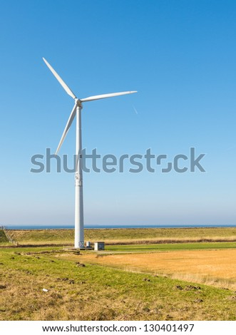 Colorful rural landscape in the Netherlands with a wind turbine against the blue sky.