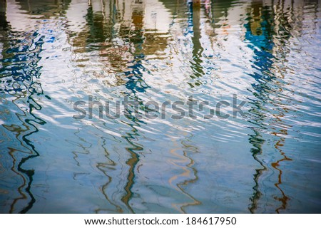 Colorful sailboats masts reflected in the waters of the harbor - stock photo