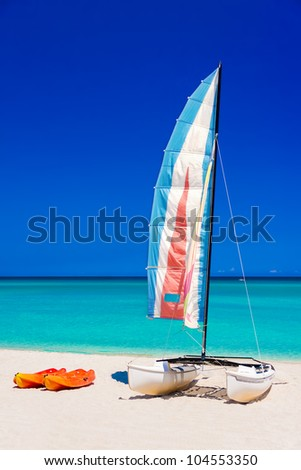 Colorful sailing boats on the  beach of Varadero in Cuba on a beautiful  summer day (vertical format without people) - stock photo