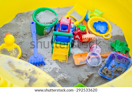 Colorful sand toys in a yellow sandbox - stock photo