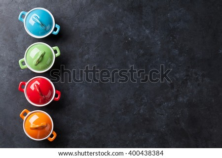Colorful saucepans on stone table background. Top view with copy space - stock photo