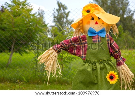 Colorful scarecrow is dressed in clothes at garden - stock photo