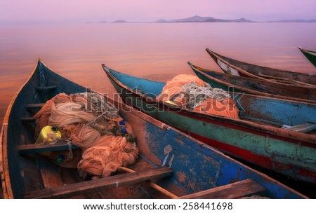 Colorful scenic sunset with fishing boats in the foreground on Mfangano Island, Lake Victoria, Kenya - stock photo