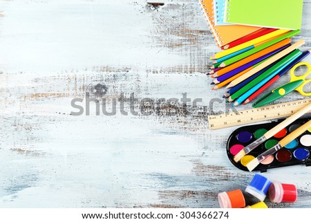 Colorful school stationery on wooden background - stock photo