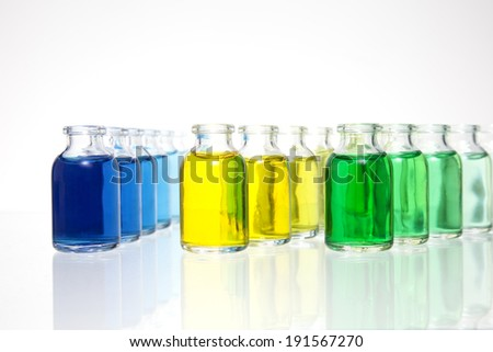 Colorful Science Vials. Several vials on a glass table top with different tones of green, yellow and blue. - stock photo