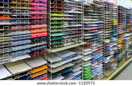 Colorful scrapbook and craft paper arranged on racks.