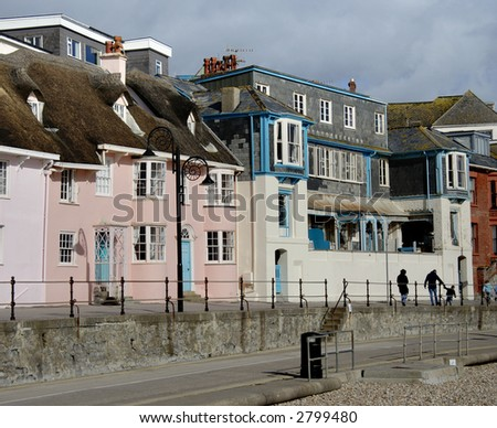 Colorful Seaside Houses in England with a family walking on the Promenade