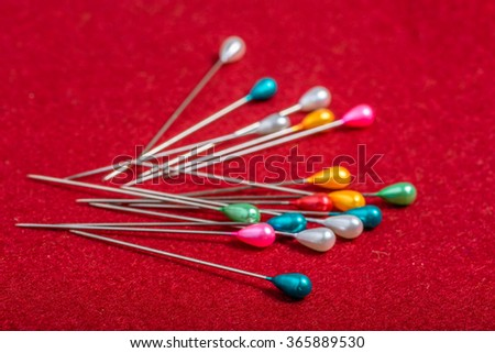 Colorful sewing pin - sewing accessories on textile background. - stock photo