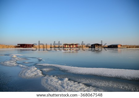 colorful shacks on frozen lake in winter - stock photo